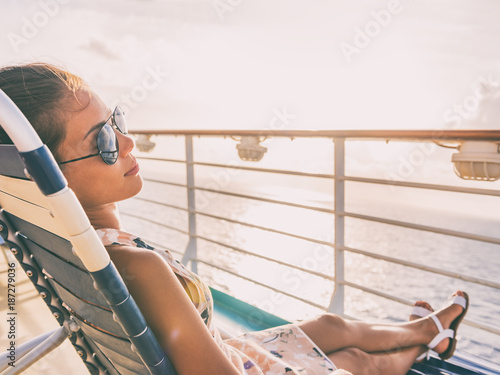 Cruise ship vacation travel woman relaxing sun tanning lying down on lounger chair on deck balcony. Suntan girl carefree with sunglasses