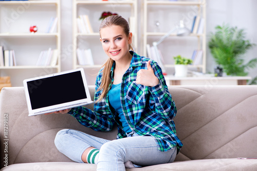 Female student sitting on the sofa with laptop - 187279852