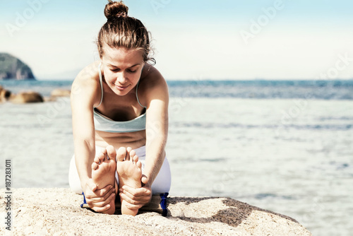 Wall mural Young woman practice yoga on the beach