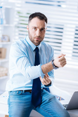 Touching sleeves. Young bearded worker sitting on the table in a comfortable modern office and touching the sleeves of a shirt while preparing to go home after a tiresome day