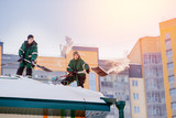 Snow cleaning. Team of male workers clean roof of building from snow with shovels in securing belts of mantra. - 187286461