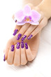 beautiful purple manicure with orchid, candle and towel on the white wooden table.