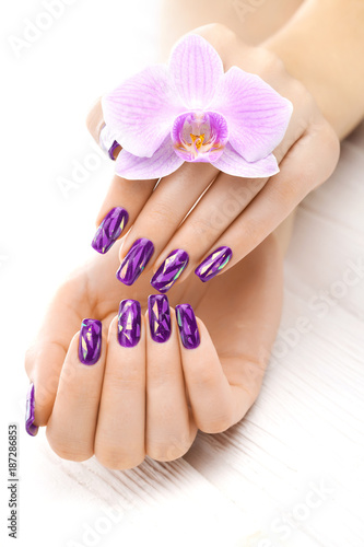 Foto op Canvas Manicure beautiful purple manicure with orchid, candle and towel on the white wooden table.