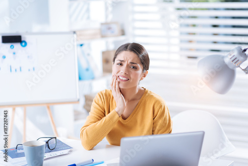 Terrible toothache. Young exhausted worker sitting at the table and touching her cheek while suffering from the unbearable toothache