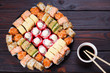 Tasty appetizing multicolored sushi rolls set, served with soy sauce and chopsticks on wooden table, view from above. Sushi restaurant concept
