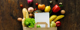 Paper bag different health food notebook wooden background Top view
