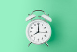 vintage alarm clock on the middle of solid light green color background