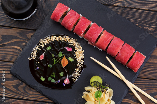 Foto op Canvas Sushi bar Japanese roll with tuna. Roll with ginger and unagi sauce on a black slate