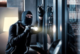 Burglary. Skilful professional masked burglar opening a window and holding a torch and breaking into the house - 187299220