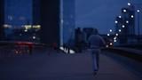 Wide shot of a hooded man walking along an empty bridge early in the morning, in slow motion - 187300645