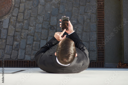 Blick von oben auf Mann der SMS schreibt