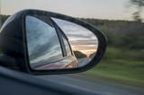 Rear window of auto with view of sundown landscape