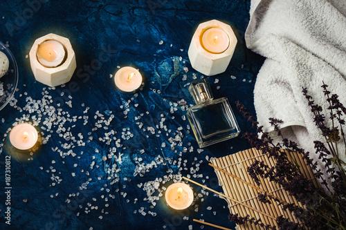 Fotobehang Spa White Towel, Sea Bath Salt, Candles, Handmade Soap on a Dark Dark Blue Background. Spa Treatments Concep