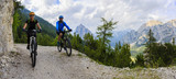 Tourist cycling in Cortina d'Ampezzo, stunning rocky mountains on the background. Family riding MTB enduro flow trail. South Tyrol province of Italy, Dolomites.