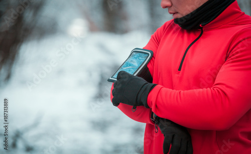 Fototapeta Runner using phone armband wearing warm running clothes, winter exercise outdoor