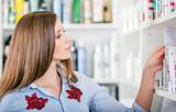 Customer woman choosing cosmetics at pharmacy store, shopping concept - 187317892