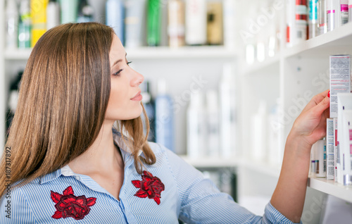 Poster Apotheek Customer woman choosing cosmetics at pharmacy store, shopping concept