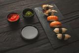 Set of sushi on black wood background, closeup