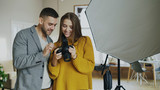 Professional photographer man showing photos on digital camera to beautiful model girl in photo studio indoors - 187326865