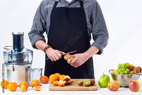 Anonymous man preparing fresh fruit juice using electric juicer, healthy lifestyle detox concept on white background. New year's resolution, fresh start, losing weight concept.