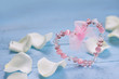 Pink heart and white roses  petals on blue wooden table. Valentine's day ,Love ,Romantic, Wedding  or Mother's day background