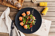 salad with vegetables, cheese and fresh salmon rolls on a black plate with a bread board and corn on a wooden table - 187334635
