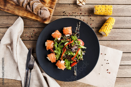 salad with vegetables, cheese and fresh salmon rolls on a black plate with a bread board and corn on a wooden table