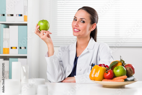 Female nutritionist holding a green apple