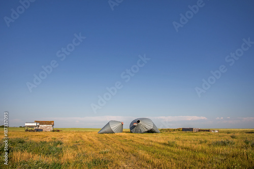 Fotobehang Natuur Two crumpled tin storage bins damaged by wind with an old shed and fuel tanks surrounded by farm fields in a rural countryside summer landscape