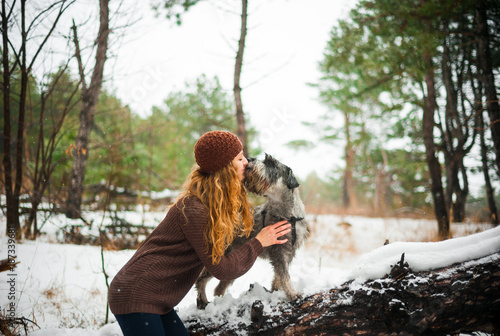 curly haired red-haired girl on a walk with a dog schnauzer in the winter aftern Poster