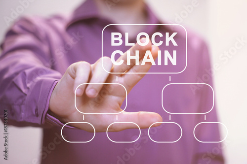 Businessman presses button blockchain on virtual digital electronic user interface.