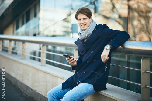Young businessman using smart phone while standing on the street.