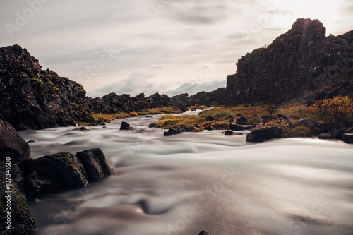 Foto Murales River Flowing from Waterfall over Volcanic Rocks Long Exposure