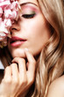 Closeup portrait of young beauty female face with blond hair and hydrangea bouquet flowers