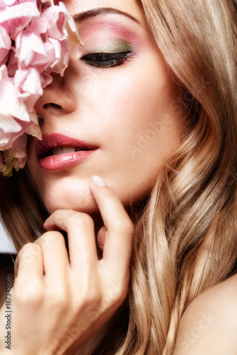 Closeup portrait of young beauty female face with blond hair and hydrangea bouquet flowers - 187345069