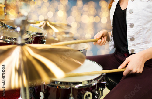 close up of woman drummer playing drum kit - 187347005
