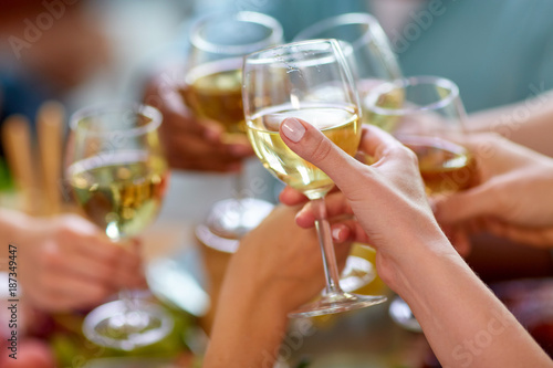 hands clinking wine glasses - 187349447