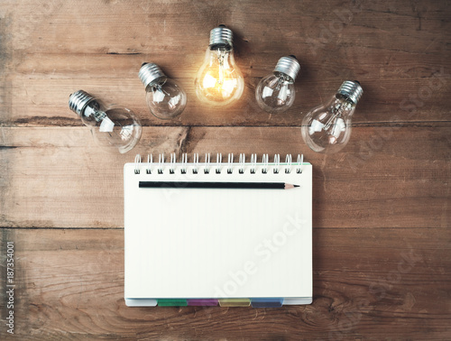 Foto Murales Notepad with pencil and light bulbs on a wood background.