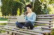 Happy young woman using laptop in park