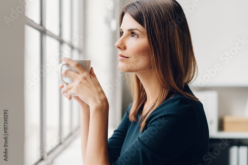Foto Murales Woman holding a cup of coffee while daydreaming