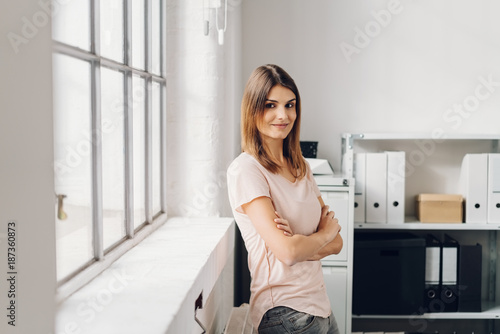 Young cheerful woman standing in office