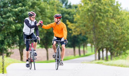 Fotobehang Fitness Racing cyclists after sport and fitness workout giving high five in finish
