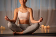 Calm young woman is meditating in peaceful atmosphere. She is sitting in lotus position on mat