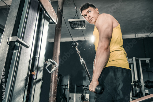 Fridge magnet Healthy man working out in gym doing triceps exercises. Photos taken on an atmospheric old gym