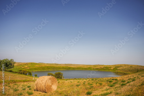 Papiers peints Miel One round straw bale by a large pond of water surrounded by a pasture fence in a rural agricultural summer countryside landscape