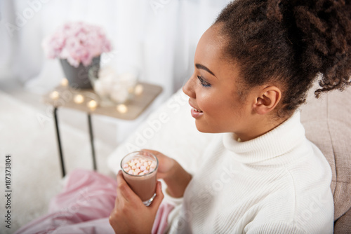 Top view profile of joyful young woman drinking hot beverage while sitting on comfortable couch. She is dreaming and smiling. Copy space