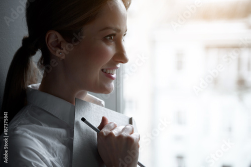 Foto Murales Side view pensive businesswoman keeping day planner in hand. Copy space. Dreaminess and labor concept