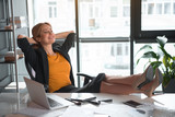 Full length portrait of friendly female having rest while situating at table in apartment. Job and leisure concept - 187376856