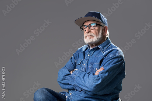 Foto Murales Want to look younger. Waist up portrait of bearded gaffer sitting on chair and looking at camera with pride. He is wearing a cap and glasses. Isolated on grey background