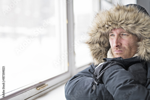 Foto Murales Man With Warm Clothing Feeling The Cold Inside House close to a window